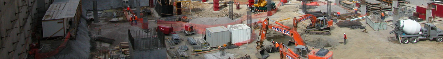 A deep construction pit filled with various heavy machinary.